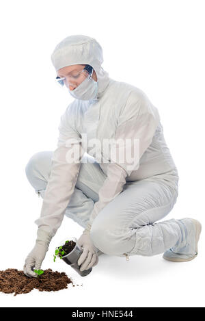 Worker in a protective suit examines the ground on a white background - Stock Photo