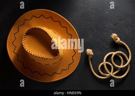 cowboy hat on black wooden background - Stock Photo