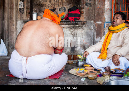 Men praying, in the Ghat of Yamuna river, Vrindavan, Mathura, Uttar Pradesh, India - Stock Photo
