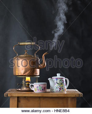 Still life with an antique boiling copper kettle, tea pot and cup - Stock Photo