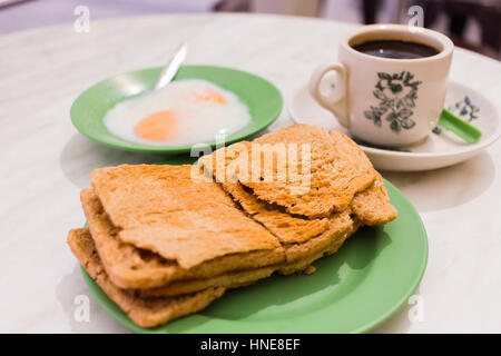 Traditional oriental Chinese coffee in vintage mug and Original bread toast with kaya a local jam made from eggs, - Stock Photo
