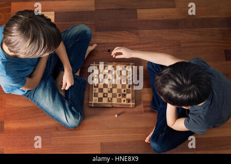 Kids playing chess sitting on wooden floor. Top view. Game, education, lifestyle, leisure concept. - Stock Photo
