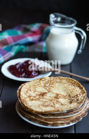 Homemade pancakes with raspberry jam on a dark wooden table. Top view with hands. Shrove Tuesday. - Stock Photo