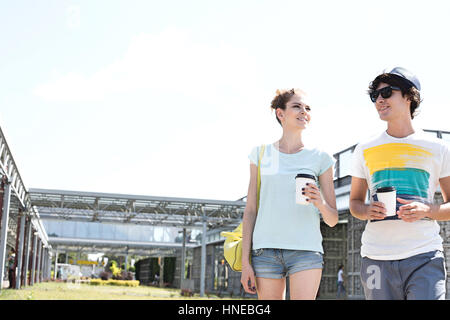 Couple holding disposable cups while walking at park - Stock Photo