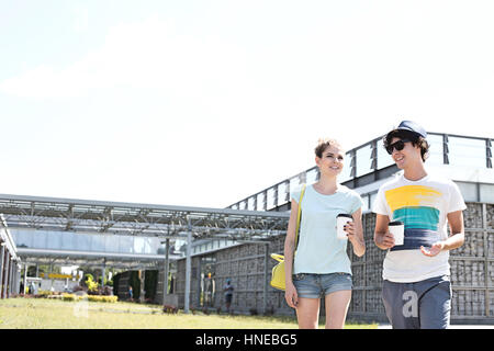 Smiling couple holding disposable cups while walking at park - Stock Photo