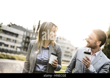 Happy business couple conversing while holding disposable cups in city - Stock Photo