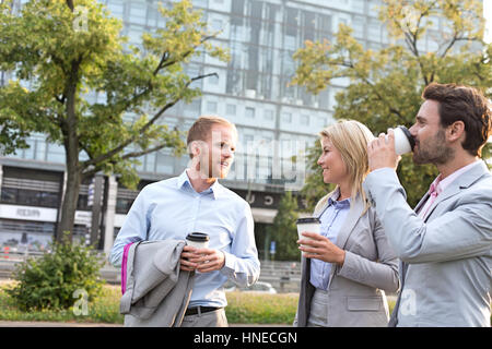 Businesspeople with disposable cups conversing in city - Stock Photo