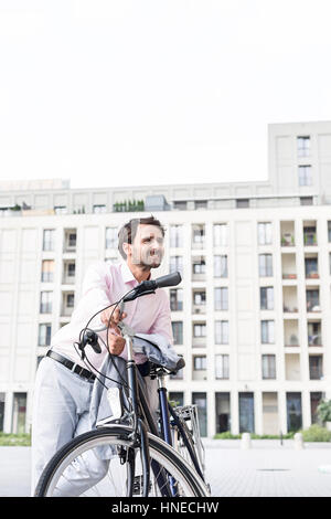 Thoughtful businessman leaning on bicycle outdoors - Stock Photo