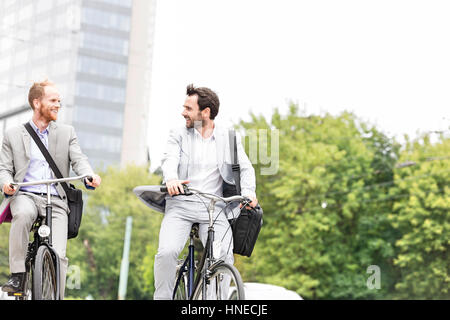 Businessmen talking while riding bicycles outdoors - Stock Photo