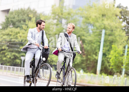Businessmen talking while cycling outdoors - Stock Photo