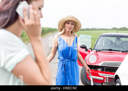 Angry woman looking at female using cell phone by damaged cars on road - Stock Photo