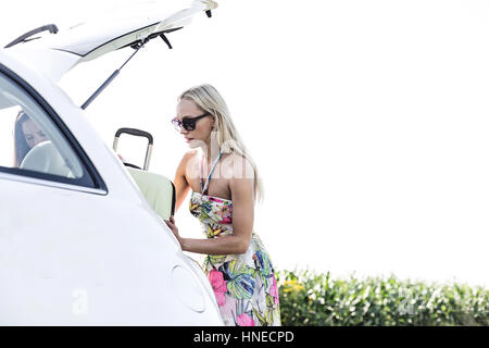 Female friends loading luggage in car trunk against clear sky - Stock Photo