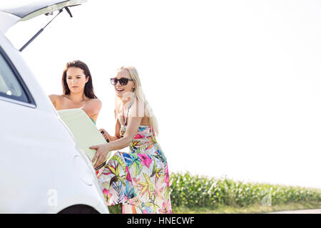 Happy female friends loading luggage in car trunk against clear sky - Stock Photo