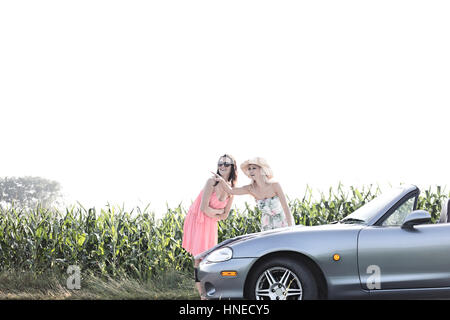 Woman showing something to female friend while reading map on convertible - Stock Photo