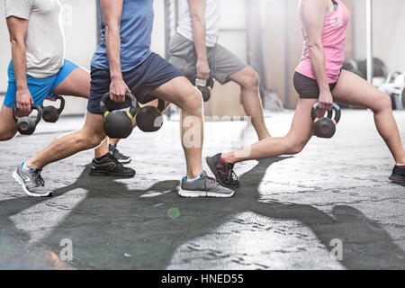 Low section of people lifting kettlebells at crossfit gym - Stock Photo