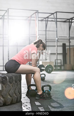 Tired woman sitting on tire in crossfit gym - Stock Photo