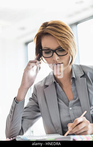 Young businesswoman on call while writing at desk in office - Stock Photo