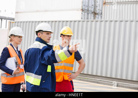 Workers discussing in shipping yard - Stock Photo