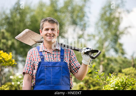 Portrait of happy man carrying spade on shoulder in plant nursery - Stock Photo