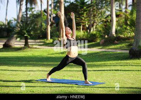 Attractive woman practices yoga in nature.. - Stock Photo