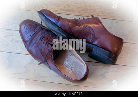 A pair of men's brown leather brogues on wooden flooring, shot from above. - Stock Photo