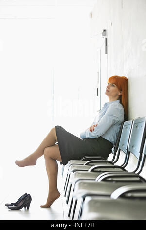 Thoughtful businesswoman sitting with legs crossed on chair in office - Stock Photo