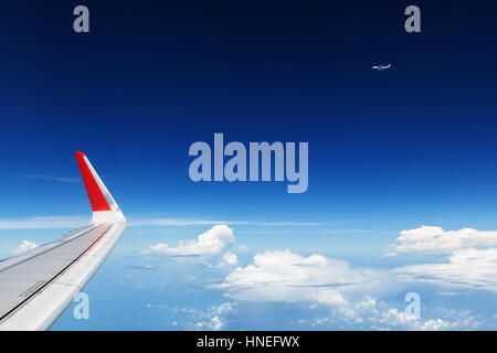 Oncoming flight traffic in mid air. Plane flying above beautiful earth, clouds. Aerial view of clear blue sky, aircraft - Stock Photo