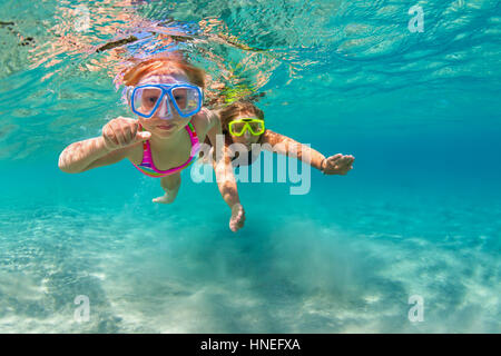 Happy family - mother with baby girl dive, swim underwater with fun in sea pool. Lifestyle, active parent, people - Stock Photo