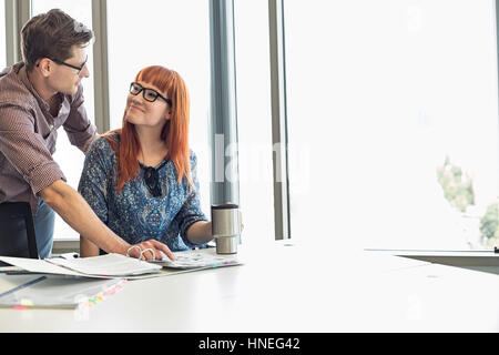 Businesspeople looking at each other while working at desk in creative office - Stock Photo