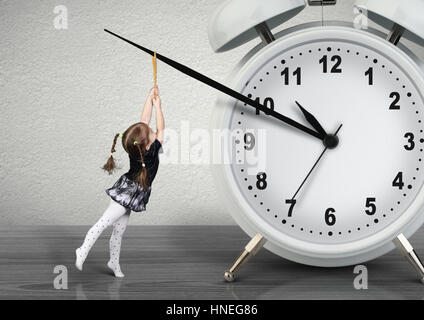 Little child girl pulling hand clock, time management concept - Stock Photo
