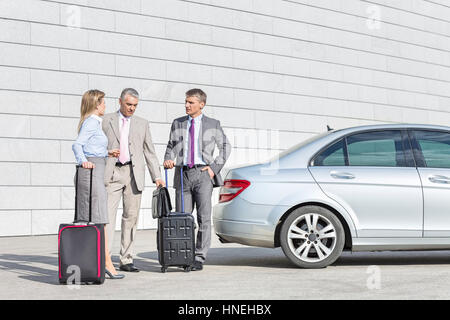 Businesspeople with luggage discussing outside car on street - Stock Photo