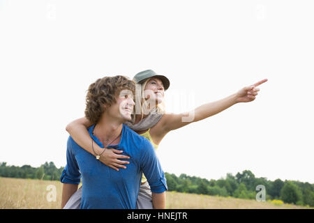 Happy woman showing something while enjoying piggyback ride on man in field - Stock Photo