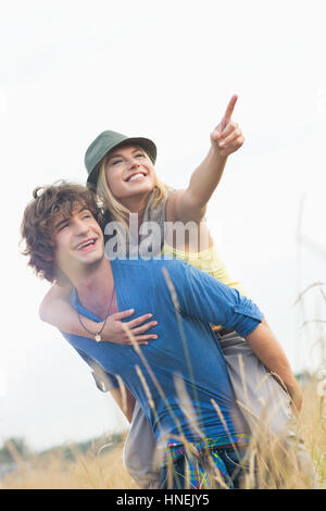 Cheerful woman showing something while enjoying piggyback ride on man in field - Stock Photo