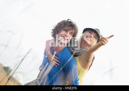 Happy woman enjoying piggyback ride on man in field - Stock Photo