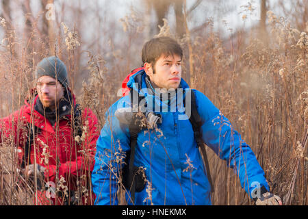 Young male hikers walking through field - Stock Photo
