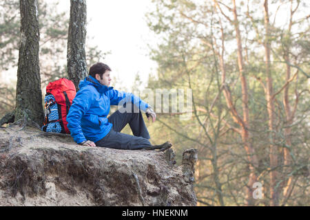 Side view of hiker sitting on edge of cliff in forest - Stock Photo