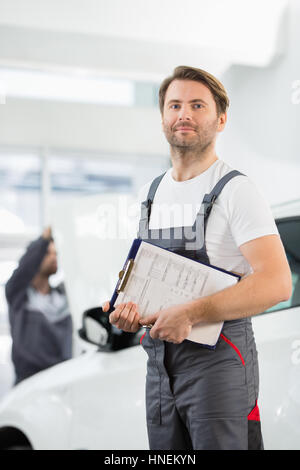 Portrait of confident male automobile mechanic with clipboard in car repair store - Stock Photo