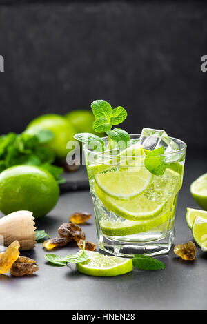 Summer mint lime refreshing cocktail mojito with rum and ice in glass on black background top view - Stock Photo