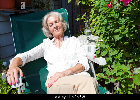Senior woman relaxing on lounge chair in garden - Stock Photo