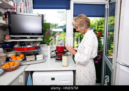 Side view of senior woman filling ground espresso in holder at kitchen - Stock Photo