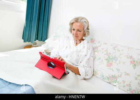 Senior woman using digital tablet on bed at home - Stock Photo