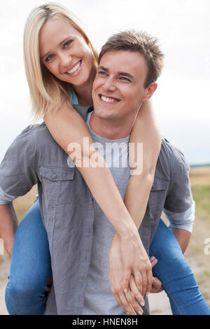 Happy young man giving piggyback ride to girlfriend on field - Stock Photo