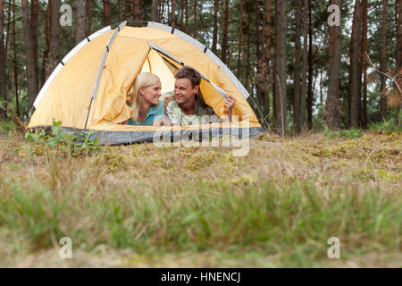 Loving young couple camping in forest - Stock Photo