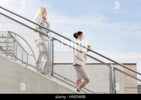 Profile shot of businesswomen holding disposable cup and mobile phone while moving down stairs together against - Stock Photo