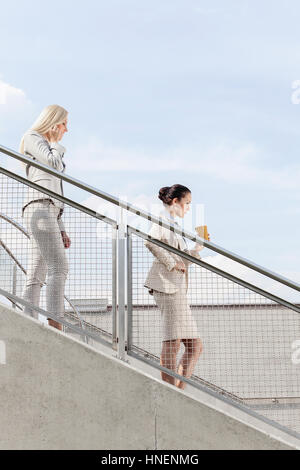 Profile shot of businesswomen moving down stairs together against sky - Stock Photo