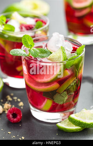 Raspberry mojito cocktail with lime, mint and ice, cold refreshing drink - Stock Photo