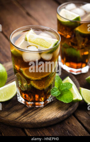 Cuba Libre cocktail with cola, lime and ice in glass, cold longdrink - Stock Photo