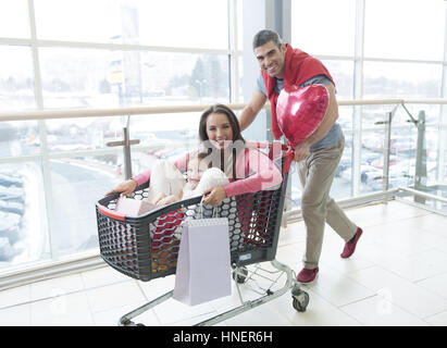 Father pushing mother and young daughter in shopping trolley - Stock Photo