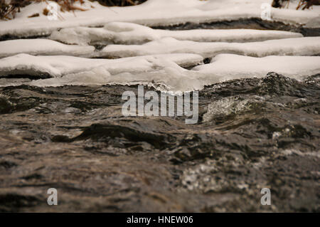 Close up of water running through partially frozen creek. Stock Photo