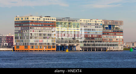 Modern residential and office building Silodam on the water on stilts, river Het IJ, Western Harbour, Amsterdam - Stock Photo